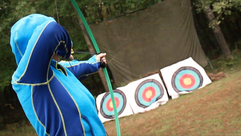 Teenager shooting a longbow