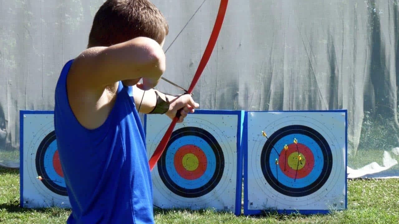 A teenage boy shooting a longbow